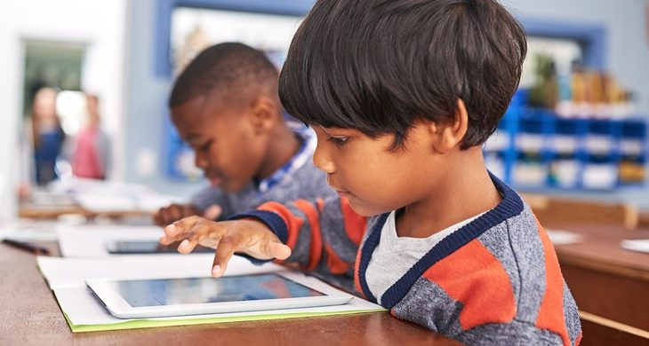 young kids using tablets in school