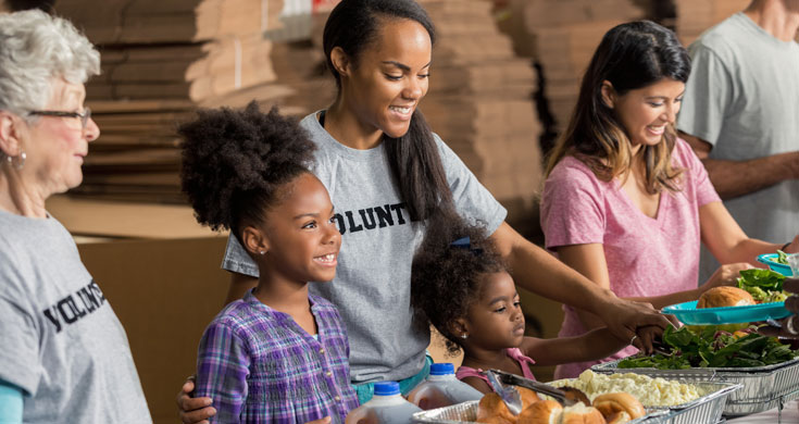 family volunteers together in soup kitchen