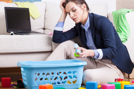 Stressed looking mother with toys on floor
