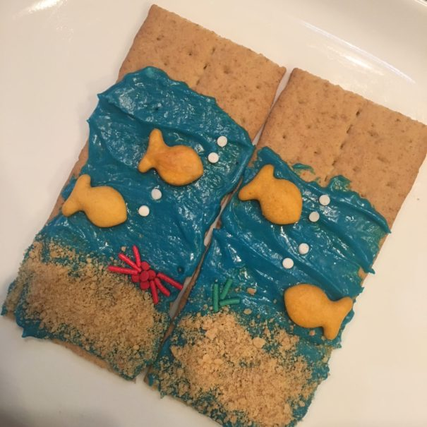 Graham crackers with blue icing, gold fish, and sprinkles