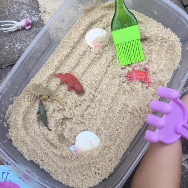 tupperware container with sand and plastic toys