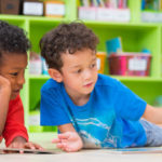 Two boys lay down on floor and reading book in preschool library