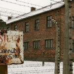 building in Auschwitz camp with old sign