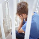 bullied child with head in hands sitting on stairs