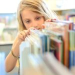 girl looking for a book in a library