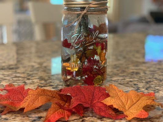 mason jar filled with water, sticks, and confetti