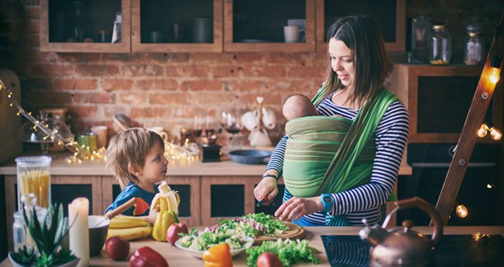 Happy young family, beautiful mother with two children, adorable preschool boy and baby in sling cooking together in a sunny kitchen.