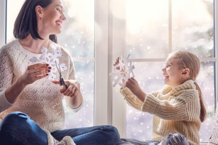mother and daughter making paper snowflakes