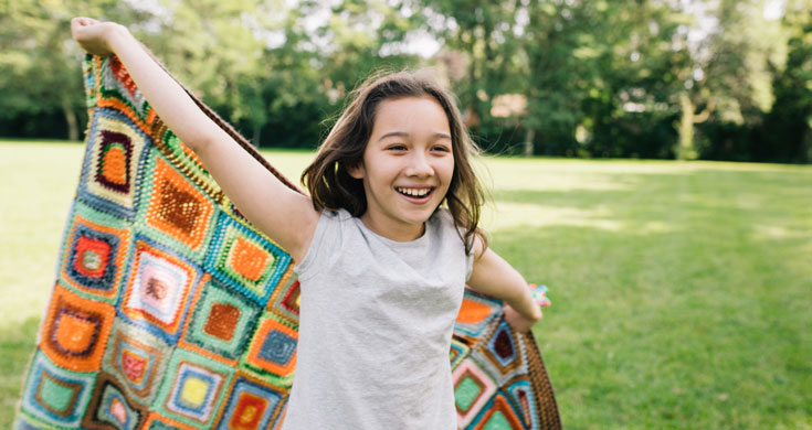 girl running with quilt in unstructured play