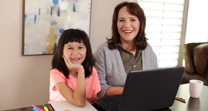 daughter and mom using laptop