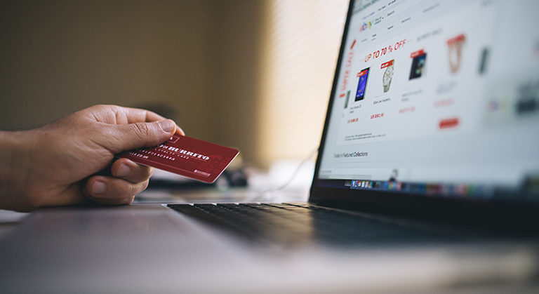 holding a credit card with laptop