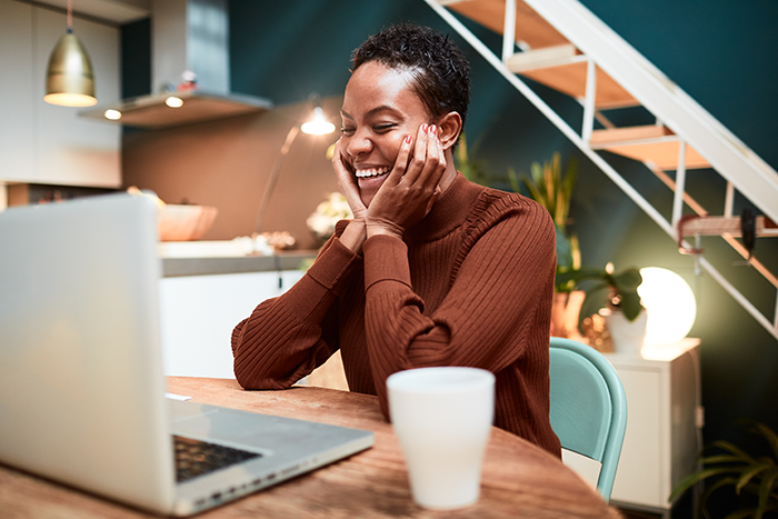 woman happily looking at her laptop
