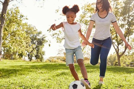 mom and daughter playing soccer