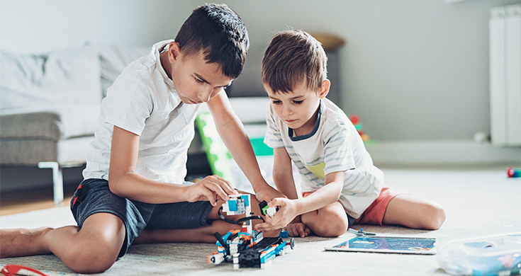 Two boys building a robot