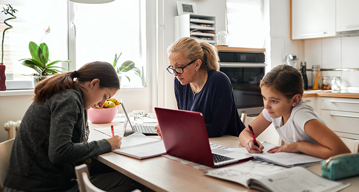 mother and her two daughters doing work and school work at a table together at home