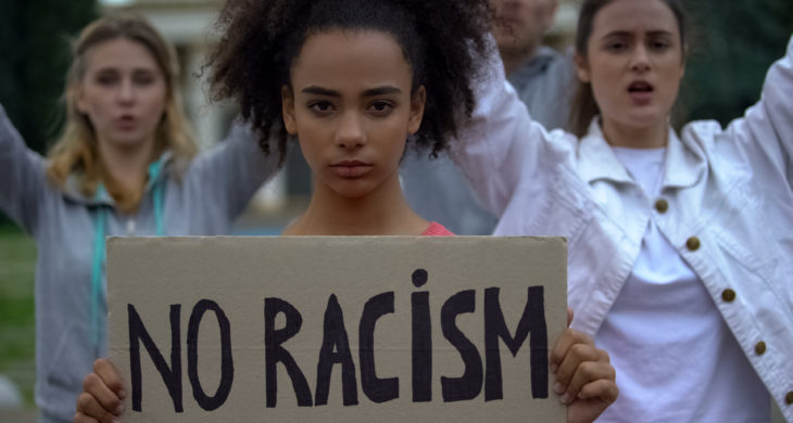 young girl holding No Racism sign
