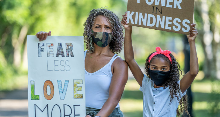 mother and daughter holding protest signs