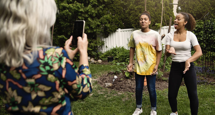 sisters being filmed by mother in backyard